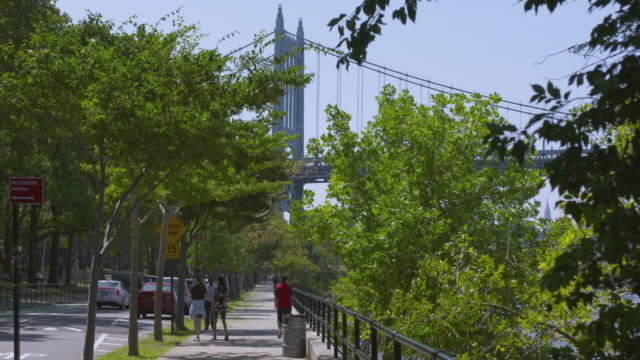 Pedestrians walk along Shore Blvd beneath the Triborough Bridge in Astoria Park.
