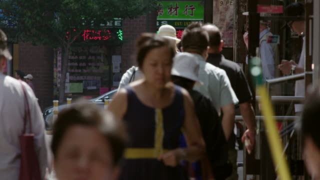 pedestrians walk along sidewalk in chinatown. man smokes cigarette in front of shop. - 言語点の映像素材/bロール