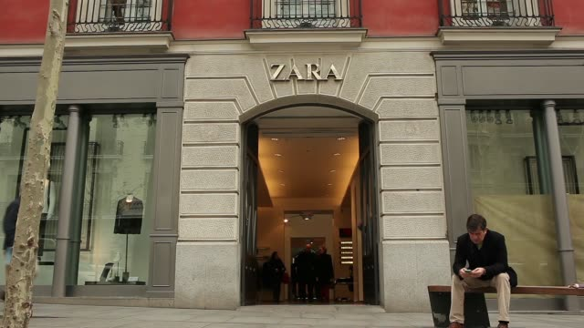 Pedestrians walk along street and customers enter a Zara fashion store operated by Inditex SA in Madrid A man sits on a bench outside a Zara store in...