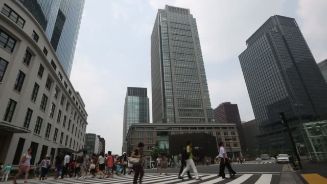 Pedestrians walk along the colonnade at the base of a building in the central business district of Tokyo Japan on Monday Aug 12 Commercial buildings...