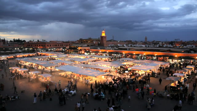 pedestrians walk along the djemaa el-fna night market at the town square of marrakesh, morocco at dusk. - nachtmarkt stock-videos und b-roll-filmmaterial