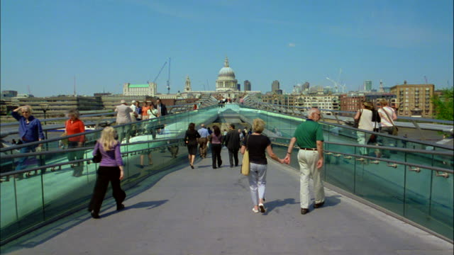 pedestrians walk along the millennium footbridge in london, england. - london millennium footbridge stock videos & royalty-free footage