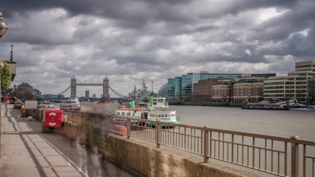 Pedestrians walk along the North embankment of the river Thames with views of rapidly moving river traffic the South Embankment and Tower Bridge