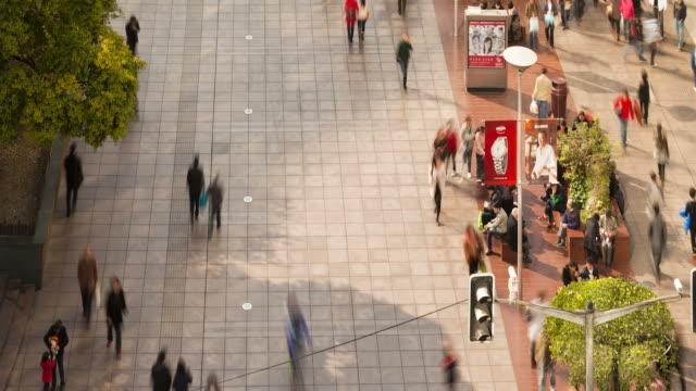 pedestrians walk along the sidewalk and street of nanjing road. - nanjing road stock videos & royalty-free footage