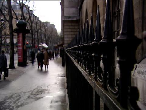 pedestrians walk alongside iron railings on side of building paris - railings stock videos & royalty-free footage