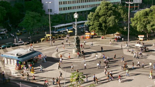 vídeos de stock, filmes e b-roll de pedestrians walk around a plaza and clock in largo da carioca in rio de janeiro. - praça
