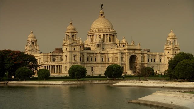 pedestrians walk around a pond in front of the victoria memorial hall in india. - victoria memorial kolkata stock videos and b-roll footage