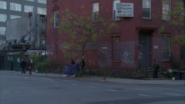 Pedestrians walk around a street corner as traffic moves through a rundown neighborhood in New York City.