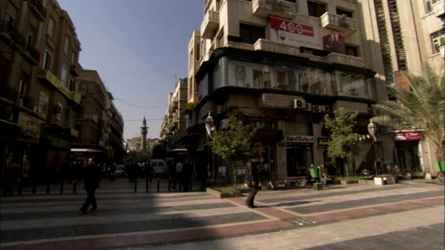 Pedestrians walk around an old town square in Damascus Syria. Available in HD.