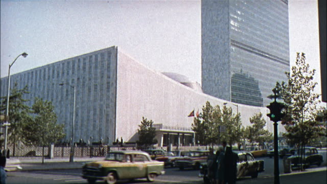 pedestrians walk around the united nations building as a woman sits on a bench and paints. - onu video stock e b–roll