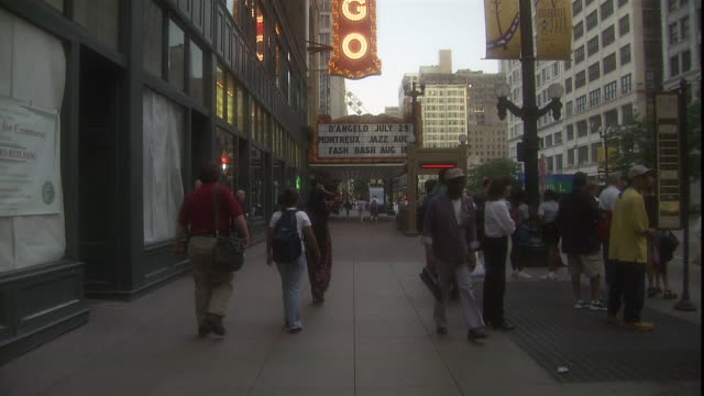 pedestrians walk beneath the illuminated sign for the chicago theater in chicago, illinois. - theatre banner commercial sign stock videos & royalty-free footage