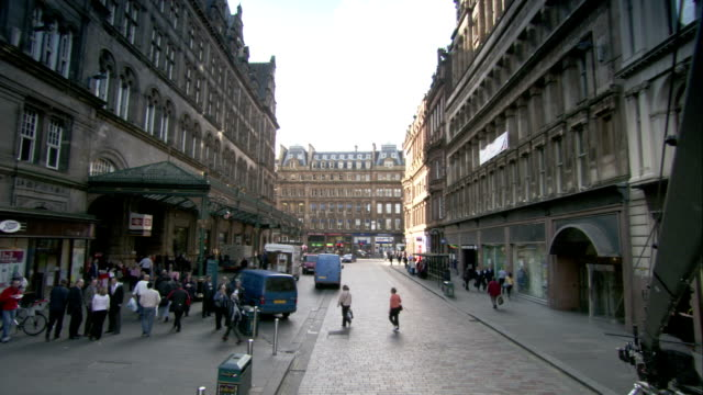 Pedestrians walk between Victorian buildings in Glasgow, Scotland. Available in HD.