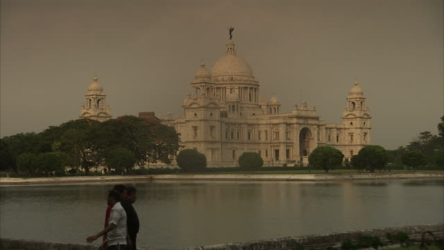 pedestrians walk by a pond in front of the victoria memorial hall in india. - victoria memorial kolkata stock videos and b-roll footage