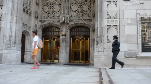vídeos y material grabado en eventos de stock de pedestrians walk by chicago tribune signage engraved on the side of the tribune tower in chicago illinois us august 6 2015 shots commuters walk by... - torre del chicago tribune