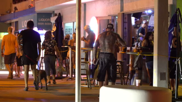 pedestrians walk by patrons enjoying a few drinks at tables set up outside the elbo room bar at the corner of las olas and fort lauderdale beach... - scott mcpartland stock videos & royalty-free footage