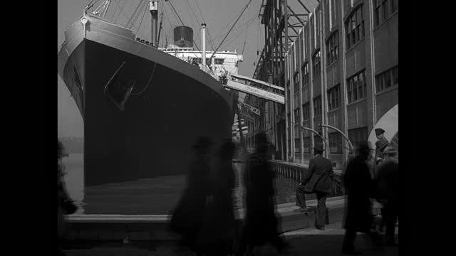 pedestrians walk by the ocean liner ile de france docked in new york. - pier stock videos & royalty-free footage