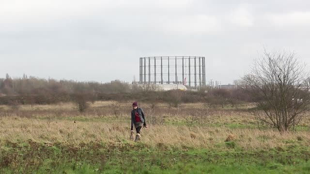Pedestrians walk dogs in Wormwood Scrubs park near the site of brownfield land with government plans to deliver affordable housing in London UK on...