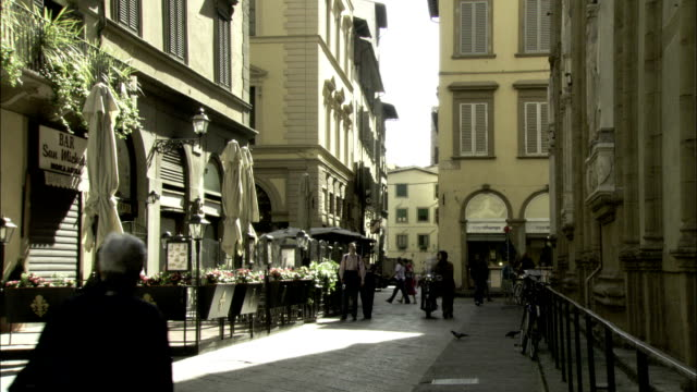 pedestrians walk down a cobbled street in florence, italy. available in hd. - florence italy stock videos and b-roll footage