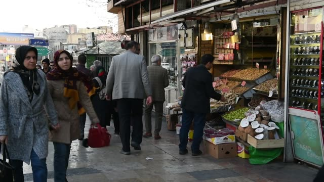 Pedestrians walk down a street and ascend an escalator in central Tehran Iran on Monday Jan 8 Customers browse fruit and vegetables at a stall