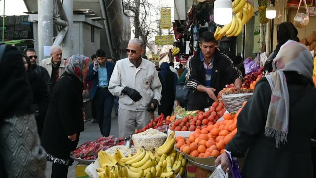 Pedestrians walk down a street in central Tehran Iran on Monday Jan 8 Customers browse fruit and vegetables at a stall