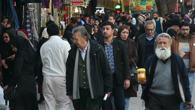 vídeos y material grabado en eventos de stock de pedestrians walk down a street in central tehran, iran, on monday, jan. 8 customers browse fruit and vegetables at a stall - vista general