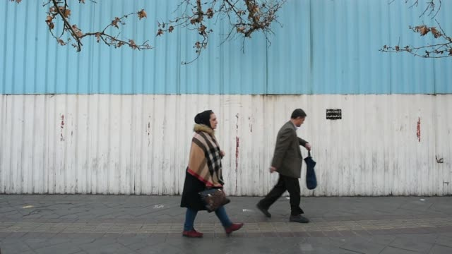 pedestrians walk down a street in central tehran, iran, on monday, jan. 8 pedestrians pass vehicles in a traffic jam - general view stock videos & royalty-free footage