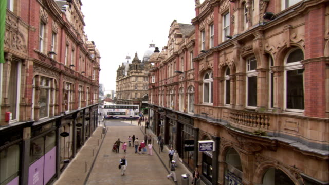 Pedestrians walk down King Edward Street in front of the Cross Arcade in Leeds, England. Available in HD.