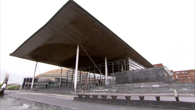 Pedestrians walk down the steps in front of the Senedd, home to the Welsh Assembly. Available in HD.