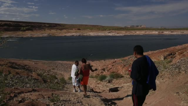 pedestrians walk down to the beach on lake powell in page arizona us on thursday june 25 2015 shots shots of pedestrians walking down steep hill to... - page arizona stock videos and b-roll footage