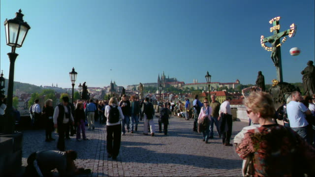 Pedestrians walk in a cobblestone plaza.