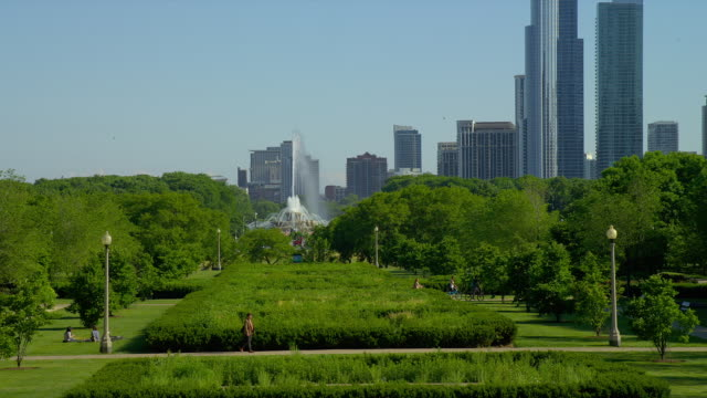 pedestrians walk in grant park in front of buckingham fountain and chicago skyscrapers. - buckingham fountain stock videos & royalty-free footage