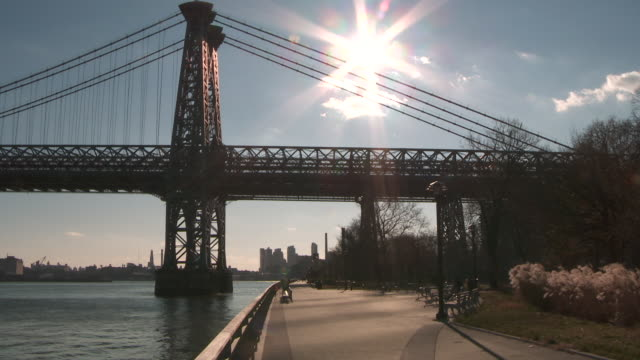 pedestrians walk in the distance on the path beneath the williamsburg bridge in manhattan with sun high in the sky and the brooklyn, boats, and the east river in the backgound - williamsburg bridge stock videos & royalty-free footage