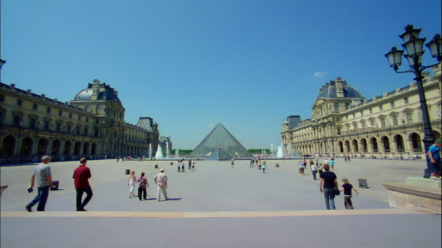 vídeos de stock e filmes b-roll de pedestrians walk in the square around the louvre palace and pyramid. - pyramid