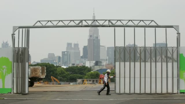 Pedestrians walk near a fence outside a construction site for a new stadium to replace the National Stadium in Tokyo Japan on Monday June 15 2015...