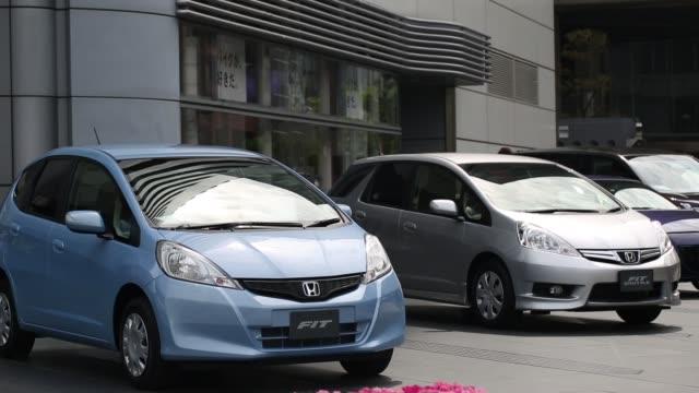 pedestrians walk near honda motor co vehicles displayed outside the company headquarters in tokyo traffic moves past the honda motor co headquarters... - ホンダ点の映像素材/bロール