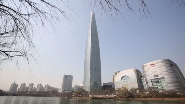 Pedestrians walk near the Lotte Corp World Tower center in Seoul South Korea on Monday March 13 Tilt up and pan left to right the Lotte Corp World...
