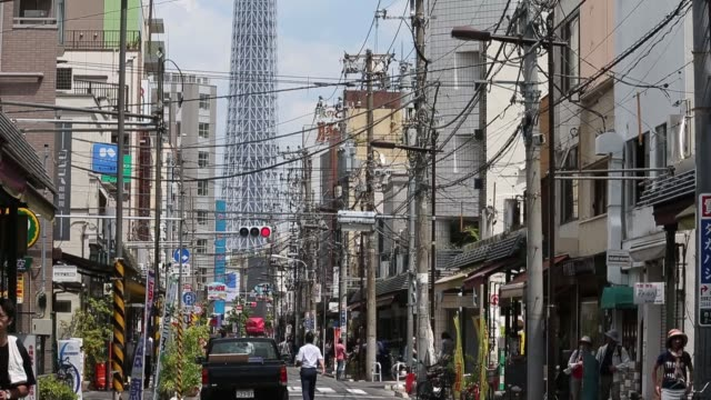 pedestrians walk on a street under power lines in front of the tokyo skytree, center, tokyo, japan, on monday, june 5 power lines hang in front of... - スカイツリー点の映像素材/bロール