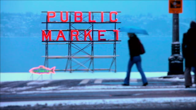pedestrians walk on an icy sidewalk past the sign for seattle's public market. - seattle stock videos & royalty-free footage