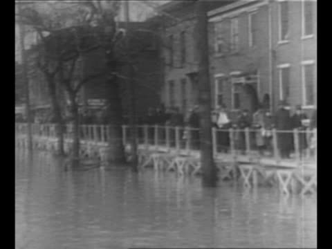pedestrians walk on sidewalk next to high waters at left as waters begin to recede after ohio river valley flood / kentucky street with mud left... - 1937 stock-videos und b-roll-filmmaterial