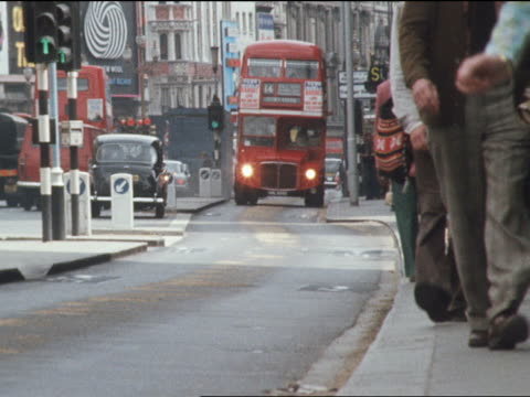 Pedestrians walk on the pavement as a red double-decker bus approaches on a Piccadilly street in London.