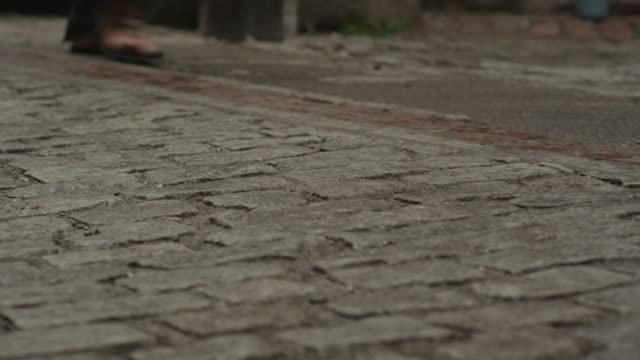 pedestrians walk on the uneven bricks of a brick street. - uneven stock videos & royalty-free footage