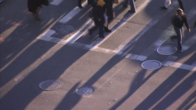 Pedestrians walk over a crosswalk near several manhole covers.
