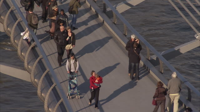 Pedestrians walk over the Millennium Bridge. Available in HD.