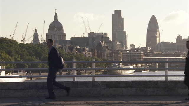 pedestrians walk over waterloo bridge with st paul's cathedral and the gherkin in the background london available in hd. - pedestrian stock videos & royalty-free footage