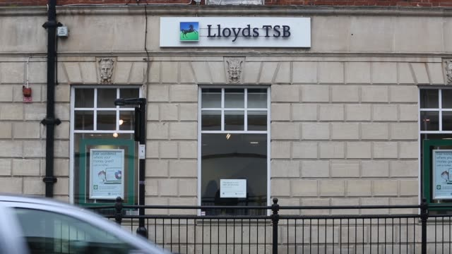 Pedestrians walk past a branch of a Lloyds TSB bank part of the Lloyds Banking Group Plc in Enfield A sign sits on a wall outside a branch of a...