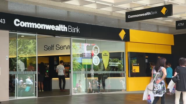 Pedestrians walk past a branch of the Commonwealth Bank of Australia in Sydney Australiaon Tuesday Feb 10 Customers enter a Commonwealth Bank of...