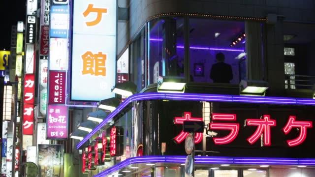 Pedestrians walk past a BV Corp karaoke facility center in Tokyo Japan on Thursday Dec 11 Medium shot seen through window of building of customers...