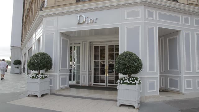 Pedestrians walk past a Christian Dior SA fashion store in Paris France on Saturday Aug 9 A porter stands outside a Dior store as pedestrians walk...