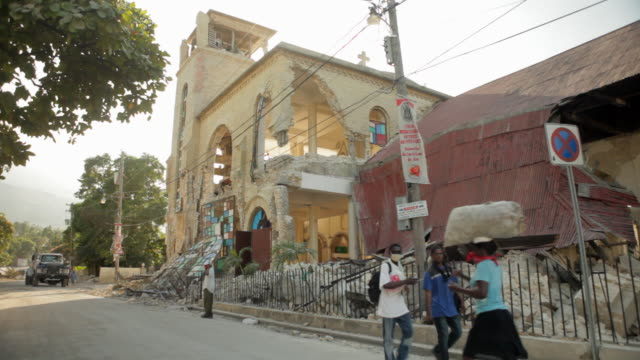 pedestrians walk past a church destroyed by the haiti earthquake of january 2010 - port au prince stock videos & royalty-free footage