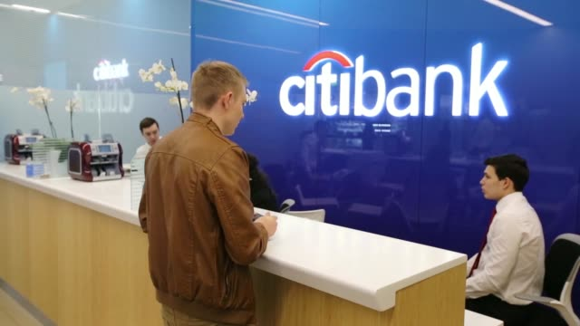 Pedestrians walk past a Citibank bank branch operated by Citigroup Inc in Moscow Russia on Tuesday April 22 Employees work behind the service desk...